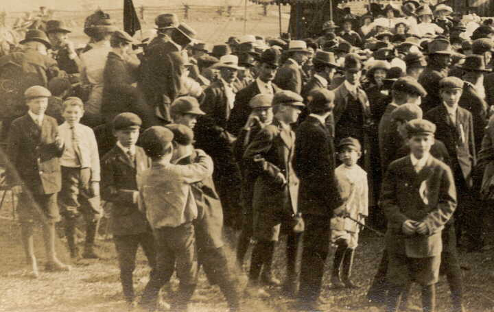Photograph of some people in crowd around fair or circus tent
